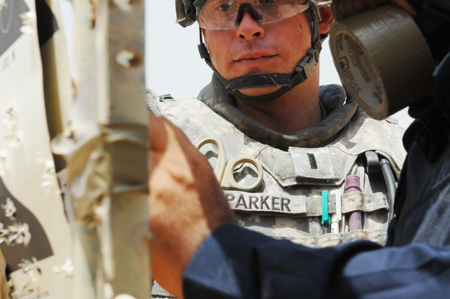 """BAGHDAD - First Lt. Chris Parker, a platoon leader from Lansing, Kan., assigned to the 300th Military Police Company, 91st MP Battalion, 8th MP Brigade, helps hang up targets with Iraqi Police commissioner Ahmed Mohammed Abdullah, assigned to the al-Qahira IP Station, before a live-fire exercise at Joint Security Station Shuleik, here, May 21. """"I've done a few ranges and this is good,"""" said Parker. """"This is IP led, IP taught and IP ran."""""""