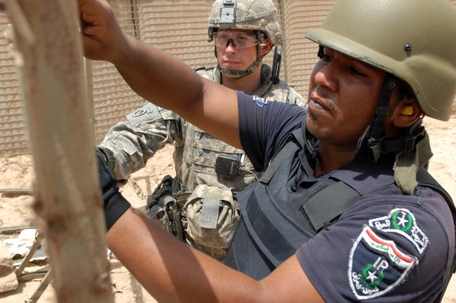 BAGHDAD - First Lt. Chris Parker, a platoon leader assigned to the 300th Military Police Company, 91st MP Battalion, 8th MP Brigade, gives a hand to Iraqi policeman Barkaat Jonaa Mohassen, assigned to the al-Qahira IP Station, during the final event of an Iraqi Primary Leadership Development Course at Joint Security Station Shuleik, here, May 21. The IPLDC graduated 21 IPs during a 5-day course where the IPs led, taught and ran the classes, said the Lansing,