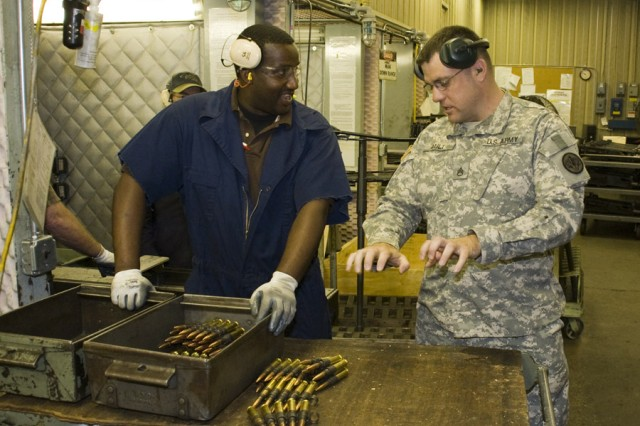 Staff Sgt. Chad Ault with the 3rd Armored Cavalry Regiment discusses range testing with Anniston Army Depot small arms repairer Daniel Garrett.