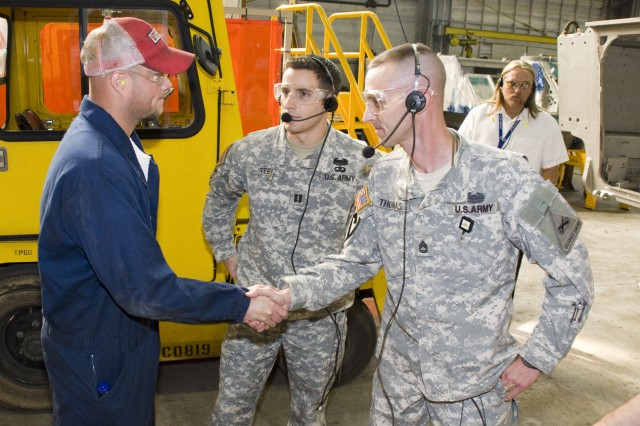 Capt. Mike Teel and Sgt. 1st Class Jacob Thomas (right) are greeted by depot machinist Randy Klinner in the depot's Nichols Industrial Complex. Teel said he noticed that one of the refurbished M1 tanks in line at the depot's test track was used by his unit last year in Iraq.