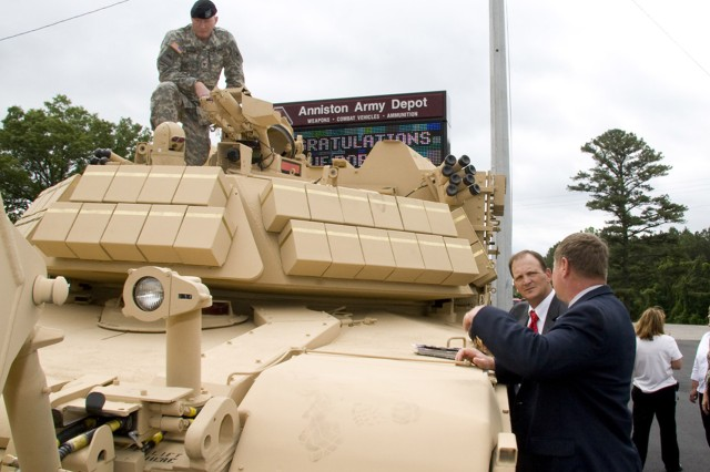A Soldier with the Army Program Executive Office scopes out the turret of an Assault Breacher Vehicle on display at Anniston Army Depot, Ala., during the May 14 roll-out ceremony.