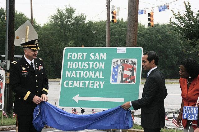 Maj. Gen. Russell Czerw, commanding general, Fort Sam Houston and Army Medical Department Center and School and Mayor-elect Julian Castro unveil one of several new road markers to be placed along Harry Wurzbach Road. A ceremony was held May 22 at the St. Pius Church and School to announce the honorary name change to TAPS Memorial Boulevard.
