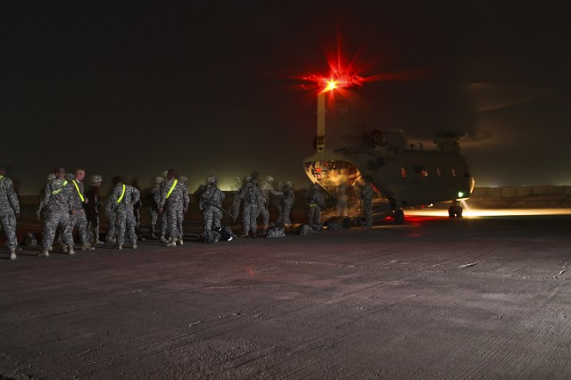CAMP TAJI, Iraq-Under the cover of night, Soldiers from the 1st Air Cavalry Brigade, 1st Cavalry Division, Multi-National Division-Baghdad, arrive at Camp Taji, Iraq, May 20, for their year-long deployment in support of Operation Iraqi Freedom. Soldiers flew in on a CH-47F Chinook helicopter from Company B, 2nd Battalion, 4th Aviation Regiment, Combat Aviation Brigade, 4th Infantry Division.