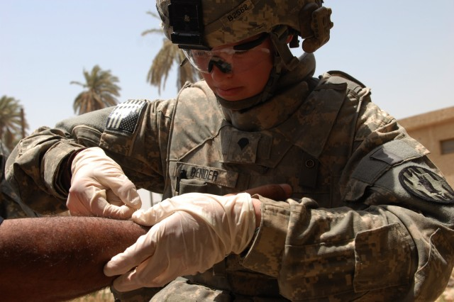 "BAGHDAD - ""I love my job and I love helping people out whether they're Americans or Iraqis,"" said Rapids City, S.D., native Spc. Megan Bender, a combat medic assigned to the 300th Military Police Company, 91st MP Battalion, 8th MP Brigade, as she treats a minor wound on an Iraqi policeman at Joint Security Station Shuleik, here, May 21. Bender and her fellow MPs are on a 15-month tour to Iraq."
