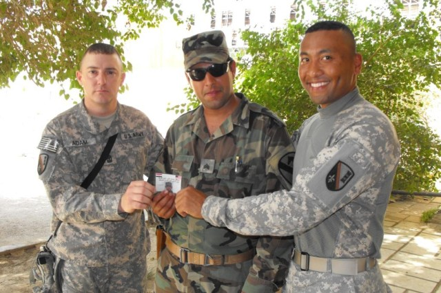 BAGHDAD - Maj. Willus Hall (right), of Dallas, and Sgt. Maj. Timothy Adam (left), from Pineville, La., present an Iraqi Army engineer a certificate of completion for attending intelligence and operations training with the 225th Engineer Brigade, May 20. As the deadline for the June 30th Security Agreement approaches, many IA Soldiers continue to receive this kind of specialized training as they take  more of an independent role on missions such as route clearance, which relies heavily on accurate intelligence gathering techniques.