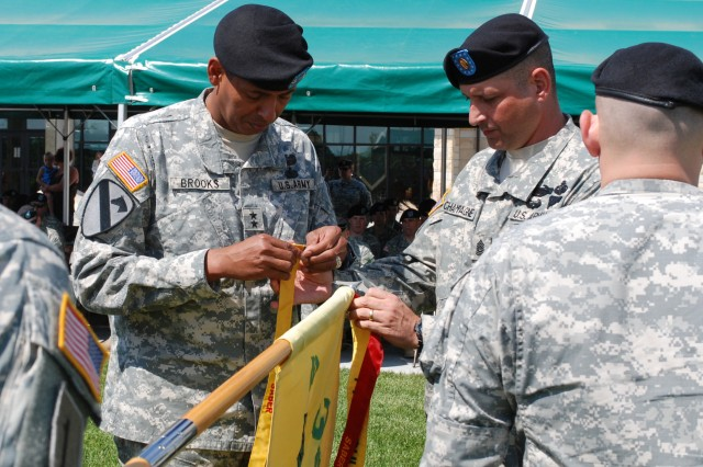 Maj. Gen. Vincent Brooks and Command Sgt. Maj. Jim Champagne, commanding general and senior noncommissioned officer of the 1st Inf. Div. and Fort Riley, place the Sober Army Bravely Expedites Readiness streamer on the guidon of Co. C, 2nd Bn., 34th Armor Regt. May 21. The unit received the gold streamer for six months without a drug or alcohol-related incident.