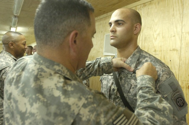 BAGHDAD - Maj. Gen. Scararrotti, commander of the 82nd Airborne Division, awards the combat action badge to Spc. Carlos Lopez-Correa, assigned to Battery B, 1st Battalion, 319th Airborne Field Artillery Regiment, 3rd Brigade Combat Team, 82nd Abn. Div., Multi-National Division- Baghdad, May 21, at Joint Security Station Zafaraniya, located in the Karradah district of eastern Baghdad. Scararrotti, along with Command Sgt. Maj. Thomas Capel, senior enlisted leader of the division, stopped to visit the Panther brigade Paratroopers deployed to Iraq.