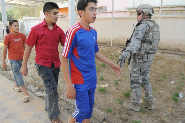 BAGHDAD - Sgt. 1st Class Daniel Workman, of Jacksonville, Fla., a platoon sergeant assigned to the Headquarters and Headquarters Troop, 5th Squadron, 73rd Cavalry Regiment, 3rd Brigade Combat Team, 82nd Airborne Division, Multi-National Division - Baghdad, greets Iraqi children during a humanitarian mission, May 19, in the Idrissi neighborhood in the Rusafa district of eastern Baghdad. Paratroopers, along with civil affairs Soldiers assigned to the 401st Civil Affairs Battalion, handed out new soccer equipment and other goods to citizens in the region in order to enhance the quality of life for citizens in the city.