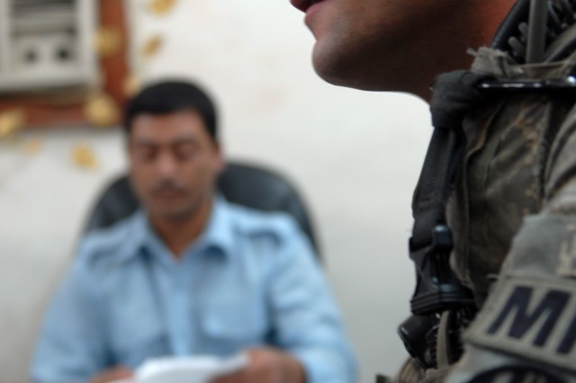 "BAGHDAD - Sgt. Jordan Talbert, a military policeman and team leader from Washington, Ind., assigned to the 300th MP Company, 91st MP Battalion, 8th MP Brigade, discusses a supply tracking system for Adamiyah District Iraqi Police Station with Ragi Shagati Abdullah, an Iraqi policeman here, May 20. ""He [Talbert] makes my job easier and gives me advice,"" said Ragi. ""We take that advice and help other IP stations."