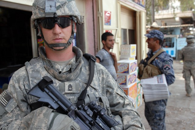 """BAGHDAD - Sgt. 1st Class Joseph Bischof, a military policeman and platoon sergeant from Louisville, Ky., assigned to the 300th MP Company, 91st MP Battalion, 8th MP Brigade, stands guard while his Iraqi Police counterpart talks with the locals in order to provide security and reassurance during a joint patrol at Kessler """"White Rose"""" Market here, May 20. The Adamiyah District IPs passed out literature and tip cards to improve trust in the local neighborhoods."""