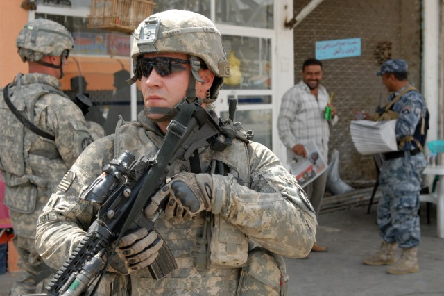 "BAGHDAD - Sgt. Jordan Talbert, a military policeman and a team leader from Washington, Ind., assigned to the 300th MP Company, 91st MP Battalion, 8th MP Brigade, provides security while an Iraqi policeman hands out newspapers in an effort to open lines of communication with local Iraqis during a joint patrol at Kessler ""White Rose"" Market here, May 20. The 300th MP Co. Soldiers have been mentoring these IPs for about 12 months. ""They [IPs] are eager to become better and eager to make their station better,"" added Talbert."