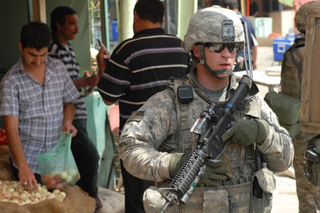 "BAGHDAD - Cpl. Brian Shipway, a native of Keyser, W.Va., a military policeman team leader assigned to the 300th MP Company, 91st MP Battalion, 8th MP Brigade, provides security during a joint patrol at Kessler ""White Rose"" Market here, May 20. According to Shipway, the MP Soldiers visit the IPs at least five times a week to provide guidance and mentorship. ""I feel that I came over here and did my job to my fullest potential,"" said Shipway. ""I go out every day and give it what I can. If I teach them one thing, it's a success in my book."""