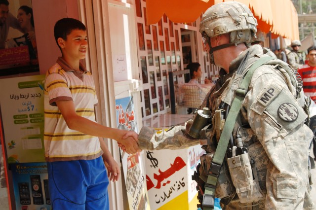 "BAGHDAD - Staff Sgt. Ryan McCarthy, a military policeman and a squad leader from Wildwood, N.J., assigned to the 300th MP Company, 91st MP Battalion, 8th MP Brigade, shakes hands with an Iraqi teenager during a joint patrol at Kessler ""White Rose"" Market here, May 20. The 300th MP Co. Soldiers have taken an over-watch role as more and more responsibility is passed to the IPs. ""When we first got here, we've been here for 11 months, we taught them how to move out in formation,"" said McCarthy. ""Now we've moved back and let them do all the talking and intelligence gathering."""