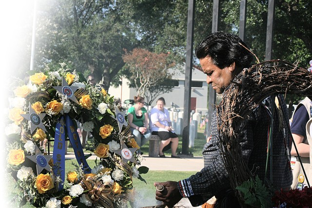 Miguel Sanchez burns sage to cleanse the area around the wreaths in honor of fallen servicemembers before the Memorial Day ceremony at the Fort Sam Houston National Cemetery.