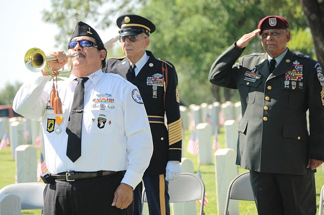 Memorial Service Detachment member Ray Gutierrez with the Tuesday Squad sounds Taps as Veterans Andrew Reyna and Fred Balderrama salute during the Memorial Day Ceremony May 25 at the Fort Sam Houston National Cemetery.