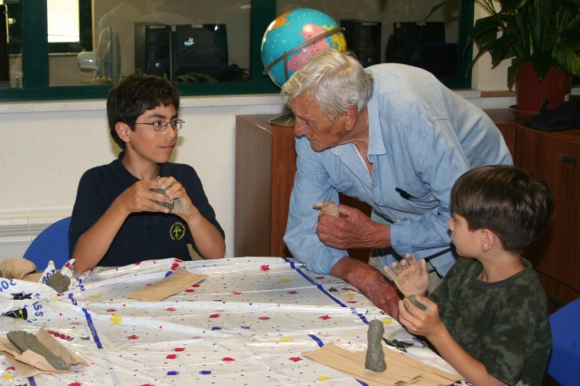 Brothers Chris and Tim Defalco get some first hand advice from Italian sculptor Ernesto Mussi during a joint Boy Scout and Youth Services after school art program at Camp Darby, Italy.