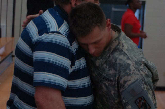 Specialist Anthony Page, 10th Trans. Co., hugs his father at his redeployment ceremony, May 25.