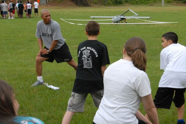 Staff Sergeant Terry Jones leads a group of students from Blackmon Middle School during a physical training session at to Essenbager Field, on Kelley Hill at Fort Benning, Ga., May 12. The seventh graders learned how and why Soldiers conduct physical training every morning.