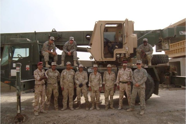 BAGHDAD- Soldiers of Company A, 46th Engineer Combat Battalion (Heavy), 225th Engineer Brigade's crane training team, along with Soldiers from 17th Iraqi Army Engineer Regiment pose in front of a 22-ton crane at Joint Security Station Knight in the Mahmudiyah district of Baghdad.