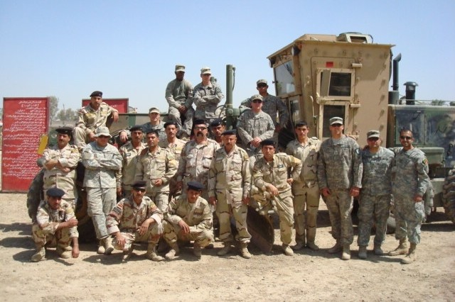 BAGHDAD - 9th Iraqi Army engineers pose with the earth movers of Company A, 46th Engineer Combat Battalion (Heavy), 225th Eng. Brigade, during a recent class on grader operations.