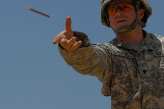 BAGHDAD - Spc. Jason Rhodes, of San Bernardino, Calif., tosses a pencil to a team mate on the site of a large expansion project at Combat Outpost Carver in southeastern Baghdad. As a specialist, Rhodes, a Company B, 46th Engineer Combat Battalion (Heavy), 225th Engineer Brigade Soldier, is in charge of the B-Hut his team is building to accommodate Soldiers moving out of the cities into the outskirts by the June 30 deadline.