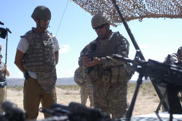 "TV personality Carson Daly receives an M9 weapons brief from Staff Sgt. John Kilburn, 11th Armored Cavalry Regiment, during his visit to the National Training Center at Fort Irwin, Calif., May 27. Daly and his film crew visited the NTC to film an episode for his late night show, ""Last Call with Carson Daly."""