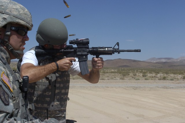 Shell casings fly as TV personality Carson Daly fires an M4 while under supervision of Staff Sgt. John Kilburn, 11th Armored Cavalry Regiment, during his visit to the National Training Center at Fort Irwin, Calif., May 27.