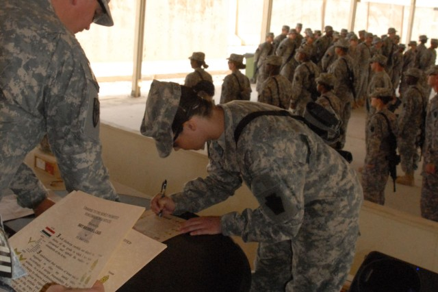 CAMP TAJI, Iraq - Sgt. Holly Brooks, of Mechanicsburg, Pa., a recently-promoted sergeant with Company C, 328th Brigade Support Battalion, 56th Stryker Brigade Combat Team, signs the noncommissioned officer charge, May 24.