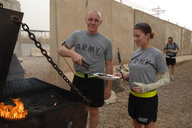 CAMP TAJI, Iraq - Despite the heat of the day and having to slave over a hot grill, Sgt. 1st Class Christopher Diehl (at left) of York, Pa. served steak with a smile May 24 to Spc. Lisa Marie Ogozaly of Coatesville, Pa. Soldiers of the 56th Stryker Brigade Combat Team's 328th Brigade Support Battalion enjoyed a Memorial Day weekend cookout following morning ceremonies which marked the recent reenlistments of 62 Soldiers, during their mobilization, and the recent promotion of 23 Soldiers to the rank of sergeant. Ogozaly did not participate in the battalion's softball game after previously injuring her arm in a volleyball game.