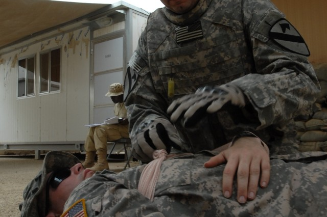 "BAGHDAD- Phoenix, Ariz. native, Staff Sgt. Bryan Champion, a psychological operations planner for 1st 'Ironhorse' Brigade Combat Team, 1st Cavalry Division, treats a ""casualty"" during a mass casualty exercise, May 22.  The exercise is part of a training program designed by brigade medical personnel in an effort to ensure all Soldiers are capable of treating wounds and reacting to attacks."
