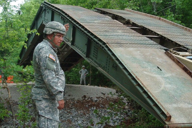 Staff Sgt. Terry Bell, 190th Engineer Company, 230th Engineer Battalion, 194th Engineer Brigade, ground guides as the Armored Vehicle Launched Bridge is lowered into place Friday at the Killebrew detour off Angels Road.