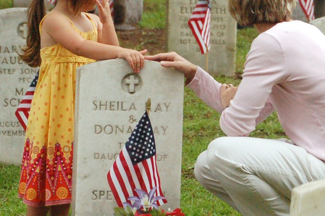 Madeline, left, and Gretchen Timmons visit the grave of twins buried in the Main Post Cemeterey before the Memorial Day Observance Monday.