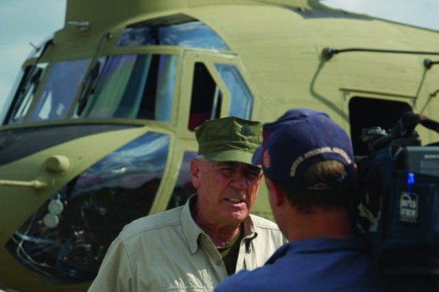 "R. Lee Ermey stands in front of a CH-47F Chinook helicopter for a segment of his show, ""Lock and Load."" Ermey, best known for his role as a drill instructor in ""Full Metal Jacket"" and the host of ""Mail Call"" came to Fort Campbell to film segments for his new show."