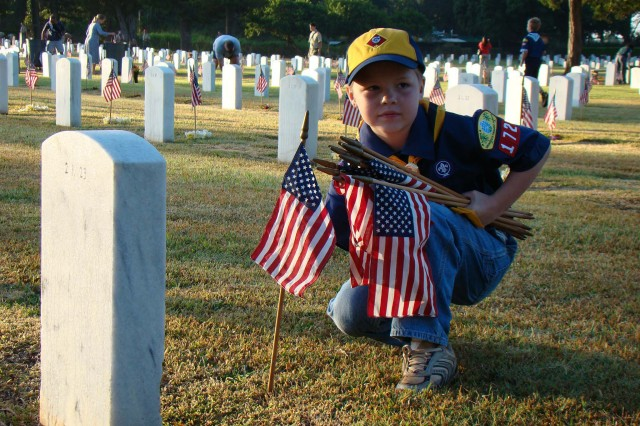SCHOFIELD BARRACKS, Hawaii - Chandler Bree, 8, of Cub Scout Pack 172, places an American flag at the foot of a gravesite at the Schofield Barracks Post Cemetery, hours prior to U.S. Army Garrison-Hawaii's Installation Memorial Day Remembrance Ceremony, May 25.
