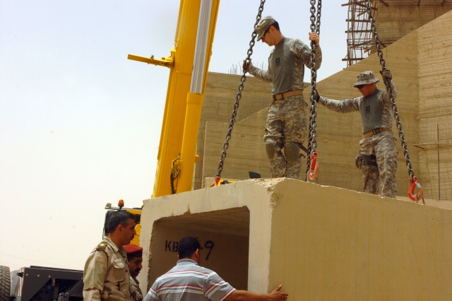 Members of the 4th Iraqi Army Division and the 4th Iraqi Army Military Transition Team, 25th Infantry Division, work together to place a concrete shelter near a construction site outside of Tikrit, Iraq, May 21. (U.S. Army photo by Pfc. Jesus J. Aranda, Task Force Lightning Public Affairs)