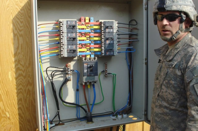 BAGHDAD- Sgt. Richard Dusenberry shows off a main distribution panel that he and his team built in support of a much needed electrical upgrade at Joint Security Site Zafaraniyah.