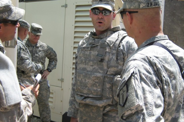 BAGHDAD- Sgt. Richard Dusenberry (center), electrician, 46th Engineer Combat Battalion (Heavy), a native of Orion, Ill., briefs Lt. Col. Matthew Zajac (right), commander, 46th Engineer Combat Battalion (Heavy), 225th Engineer Brigade and other key leaders on the electrical situation at Joint Security Station Ur after making his assessments.  Dusenberry was part of a crisis response team sent in after an attack on the JSS.
