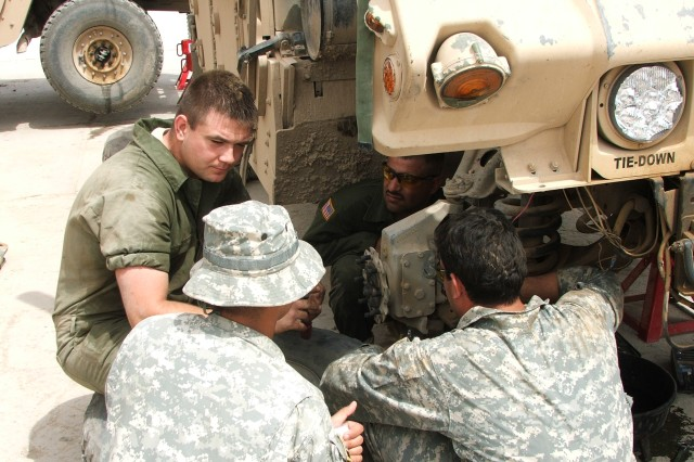 """BAGHDAD- Spc.  Olon Forrest (left), a mechanic for 1st """"Dragon"""" Battalion, 82nd Field Artillery Regiment, 1st Brigade Combat Team, 1st Cavalry Division, explains the workings of the humvee suspension system during a maintenance course hosted by the battalion.  The course is part of an ongoing effort to strengthen the security capabilities of Iraqi Security Forces."""