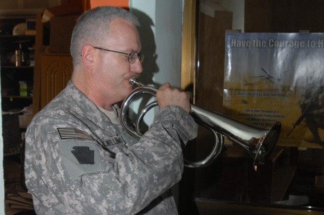 CAMP TAJI, Iraq - Master Sgt. Jon McWilliams, chaplain assistant, from Lancaster Pa., plays Taps during the Memorial Day service, May 25, at the Warrior Chapel for Soldiers of the 56th Stryker Brigade Combat Team, 1st Cavalry Division, Multi-National Division-Baghdad
