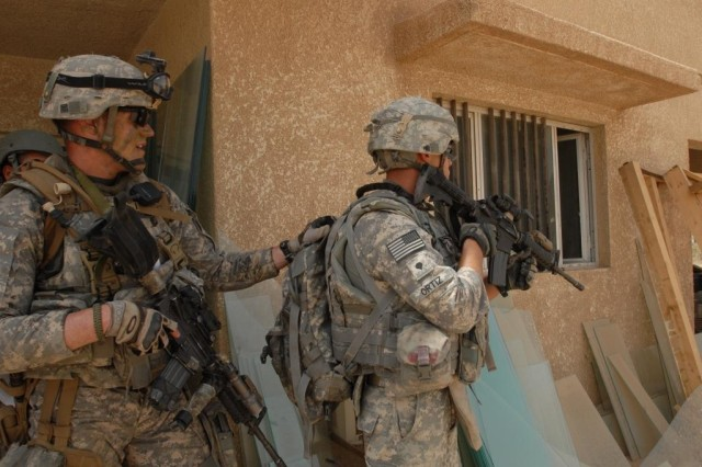 TAJI, Iraq - Staff Sgt. Paul Hanson (left) and Spec. Adam Ortiz, both of Erie, Pa, prepare to enter a building at the Nassir factory complex north of Camp Taji on May 24.  Both Soldiers are from Company B, 1st Battalion, 112th Infantry Regiment, 56th Stryker Brigade Combat Team.