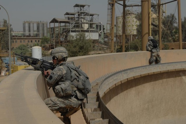 TAJI, Iraq - Soldiers from Company B, 1st Battalion, 112th Infantry Regiment,  56th Stryker Brigade Combat Team, provide over watch from a cistern at the Nassir factory complex north of Camp Taji on May 24.