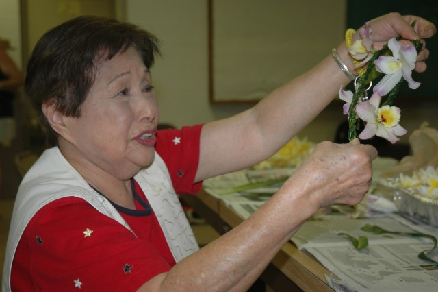 WAHIAWA, Hawaii - Frances Nagaki, a member of the Wahiawa Rainbow Seniors Club, shows a fellow lei maker the fruits of her labor. Volunteers from the Wahiawa Rainbow Seniors Club gathered May 22 to prepare the lei for the ceremony.