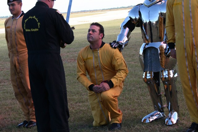 (Right)  SFC Daniel Metzdorf kneels to recite the Golden Knight Creed as he is knighted by Lt.Col. Anthony Dill (pictured with sword). (Also pictured left to right are: Staff Sgt. Christopher Acevedo; U.S.A.P.T. Knight, Joel Rowley; and Sgt. Trevor Oppenborn.)