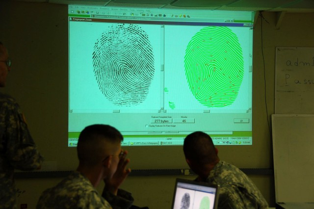 Soldiers proficient in biometric technology review minutiae points charted on fingerprints.