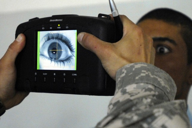 A Soldier uses the Hand Held Interagency Identify Detection Equipment System to fingerprint and photograph new Iraqi police recruits at the IP Academy in Mahmudiyah, Iraq.