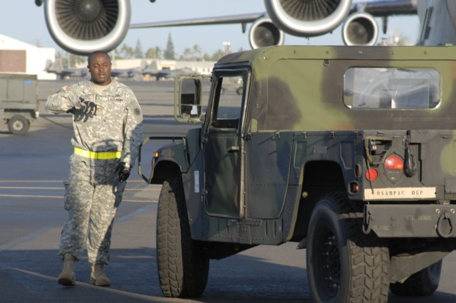 Staff Sgt. John Zahnee guides Deployable Assessment Team vehicles onto a C-17 Globemaster in preparation for a deployment to Kauai in support of Exercise Makani Pahili May 30.