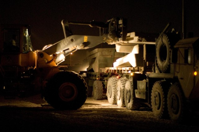 A forklift removes concrete barriers off the back of a 419th Combat Sustainment Support Battalion palletized load system vehicle at Camp Taji, Iraq May 8. The 419th CSSB is supporting the U.S.-Iraq Security Agreement by assisting in the closure of camps and joint security stations in the Baghdad area