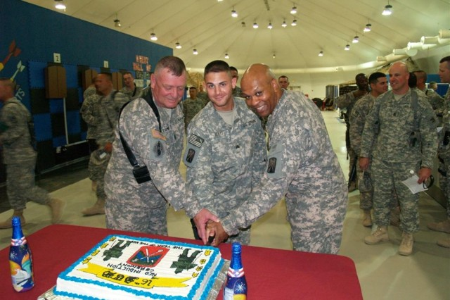"""Command Sgt. Maj. Larry Tidwell, command sergeant major, 30th Combat Sustainment Support Battalion, 16th Sustainment Brigade, Sgt. Dane Flott, 16th Sust. Bde., and Command Sgt. Maj. Johnny Godbee, command sergeant major, 16th Special Troops Battalion, 16th Sust. Bde., cut the cake after an NCO induction ceremony at the Morale, Welfare and Recreation base complex at Contingency Operating Base Q-West, Iraq, May 16. Forty six new non-commissioned officers from the 16th STB and the 30th CSSB were officially inducted into the corps of non-commissioned officers during the ceremony. Guest speaker Command Sgt. Maj. James E. Spencer, command sergeant major, 16th Sust. Bde., exhorted new non-commissioned officers to take their responsibilities seriously during the ceremony. """"Leaders are professional Soldiers that know and exude Army values. You are the very first level of authority, training, discipline and leadership in your unit. You will lead from the front, set the example and never - I stress this - you will never ask your Soldiers to do anything that you have not already done or will not do yourself."""""""