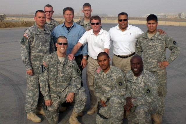 "Mark ""Ranger"" Jones poses with Ken Fisher (center) of the Fisher House Foundation and a group of Soldiers in Iraq in 2008. Jones and Fisher visited troops and hospitals in Iraq to learn first hand how to better help Soldiers in their time of"