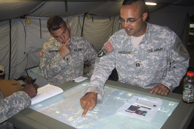 Capt. Ramon W. Almodovar, commander Alpha Co. EXFOR, 1st Battalion, 29th Infantry Regiment, Fort Benning, Ga., uses a COMET prototype to plan a mission during an exercise. The COMET team is participating to evaluate the technology and gather valuable Soldier feedback.